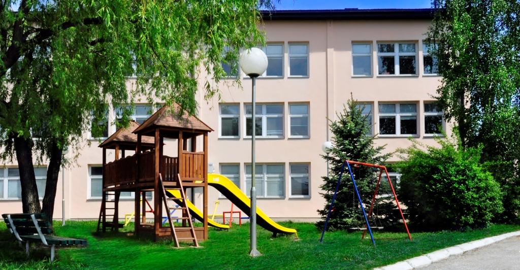 Екстеријер школе са делом игралишта и дрвеном кулом